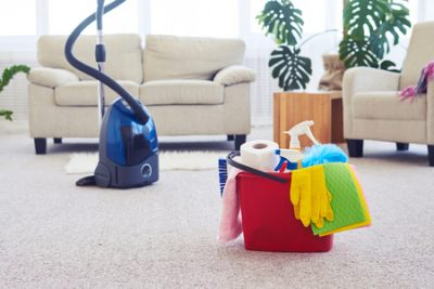 Best (traditional) cleaning products for housekeeping. Blue vacuum with red bucket full of cleaning products inside of home.
