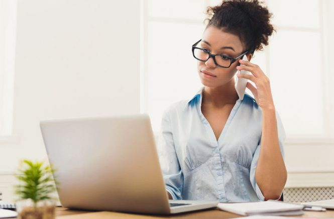 5 Questions before taking a new job. Concentrated black woman holding phone in office next to her computer.
