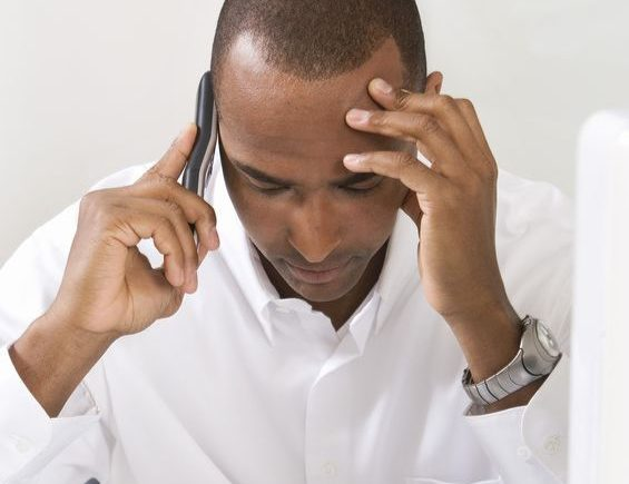 5 steps for handling difficult conversations with employees. Black man distressed holding a phone.