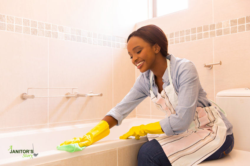 black woman smiling while claning a tub