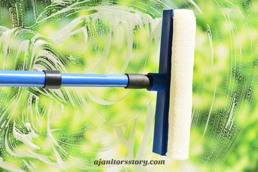 Cleaning windows with a squeegee. Home and office cleaning services.