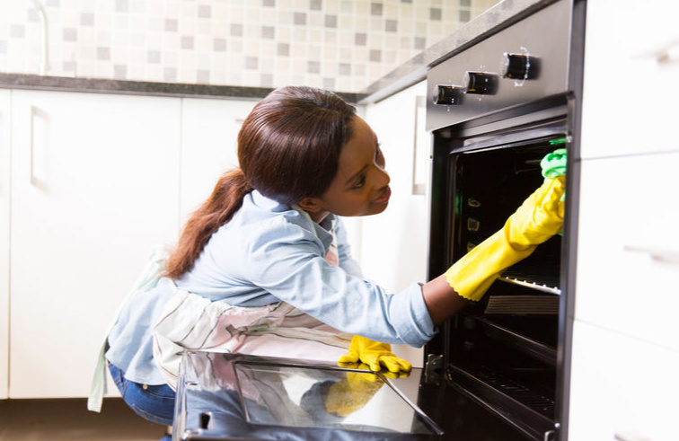 black woman cleaning an oven house cleaning business starter pack