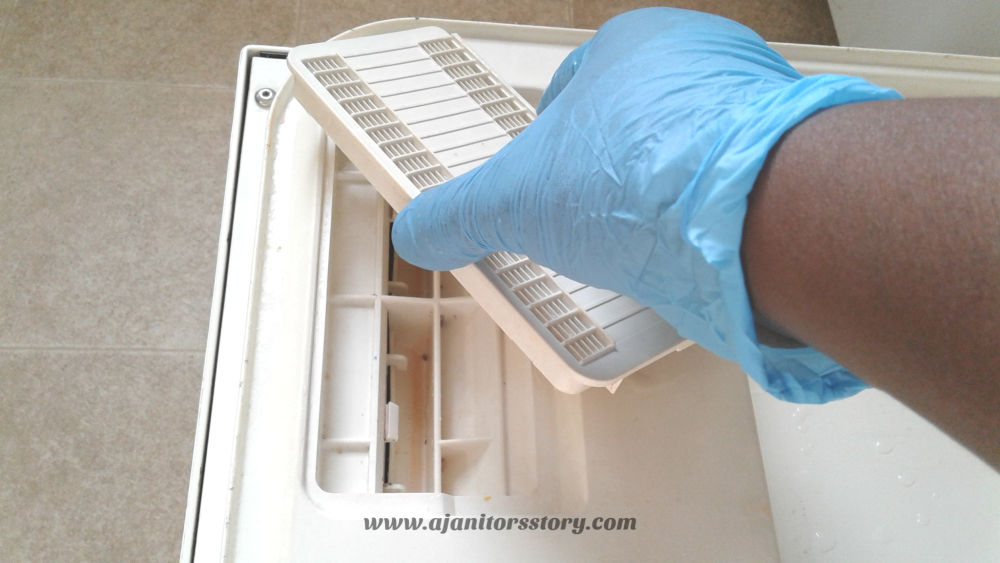 How to clean a dishwasher. Picture of a dish a beige disher washer with a blue gloved hand on dishwasher door vent.