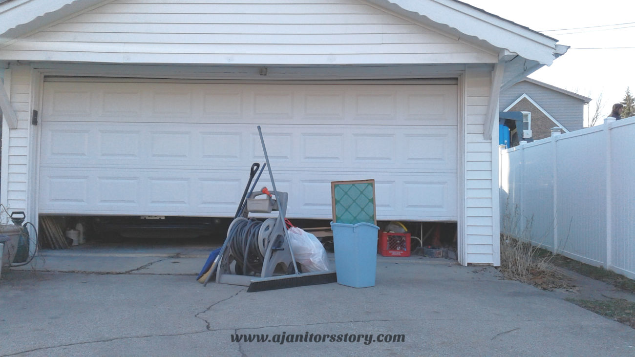 how to clean a garage. White door garage with cleaning supplies and blue trash can.