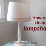 How to clean lamp shades. Off white striped lamp shade on a blue table.