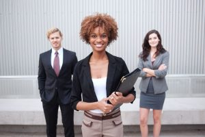 How to find more customers for my cleaning business. Black woman with co workers in back ground.