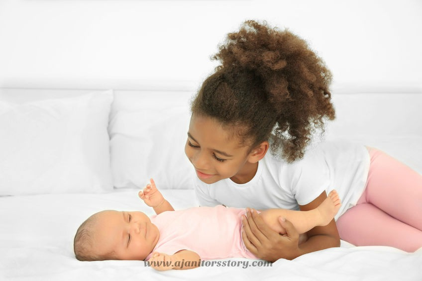 Why and how to wash sheets and towels with your cleaning comapany. Cute baby on bed with her elder sister.